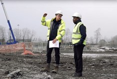 Apprentice and colleague talking on construction site