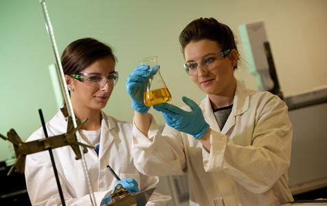 Modern Apprentice Amanda examines a beaker with a colleague in a lab while wearing a white lab coat and safety goggles