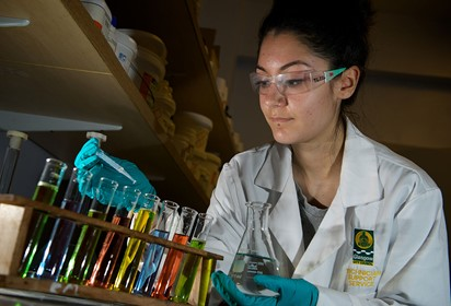 A female apprentice looks at a test tube experiment in a lab while wearing a white lab coat