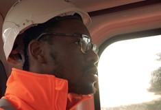 A male apprentice in a hard hat in a van