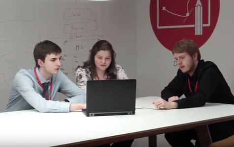Three Graduate Level Apprentices sit around a laptop in a seminar room at university.