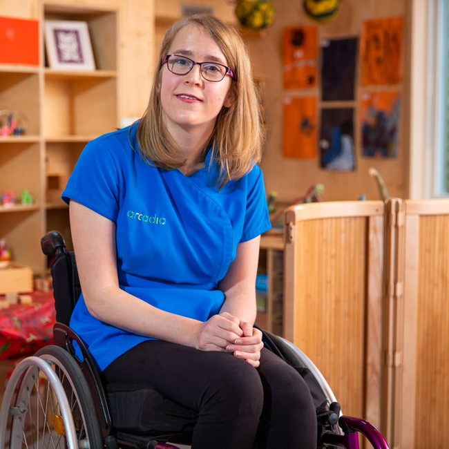 A female childcare apprentice smiling and sitting in a wheelchair in a nursery