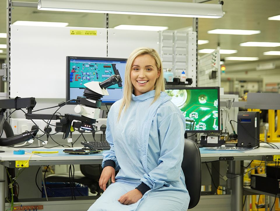 A female scientist smiles to camera in a lab while sitting next to a microscope in blue