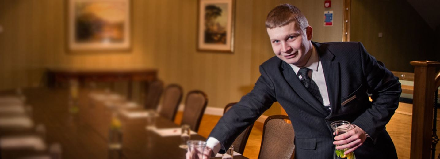 Male Modern Apprentice sets a table in a hotel conference room