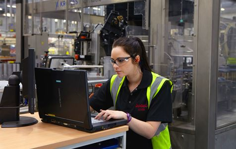 Electrical engineering Modern Apprentice Letitia types on a laptop in a Diageo bottling plant while wearing safety glasses