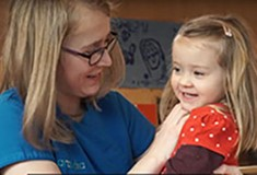 A female childcare apprentice smiling and holding a young child in a nursery