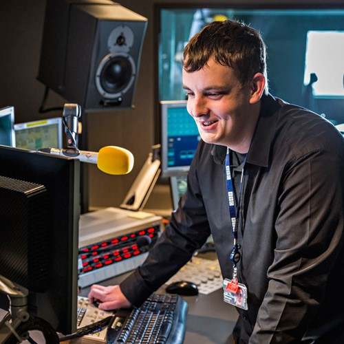 Male digital media Modern Apprentice Stewart stands in a radio studio at BBC Scotland speaking into a yellow microphone
