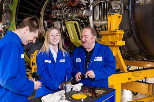 Employer laughing with two younger employees in an industrial work setting, surrounded by machinery