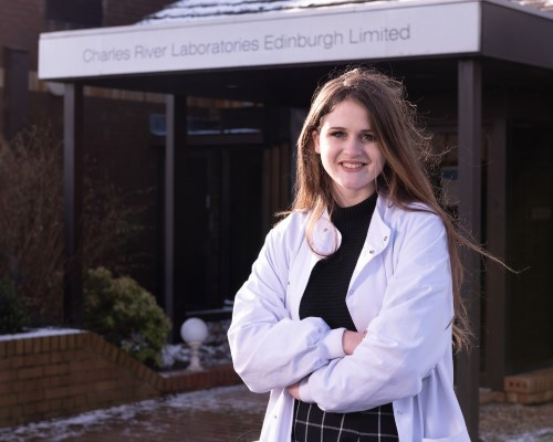 Young woman dressed in a lab coat and work clothes standing smiling outside a building which has a sign saying 'Charles River Laboratories Edinburgh Limited'