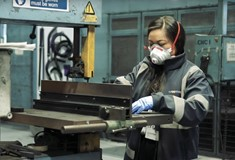 A female graduate apprentice working in an engineering workshop with a small mask and hi-vis jacket on
