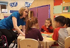A female childcare apprentice working with young children in a nursery