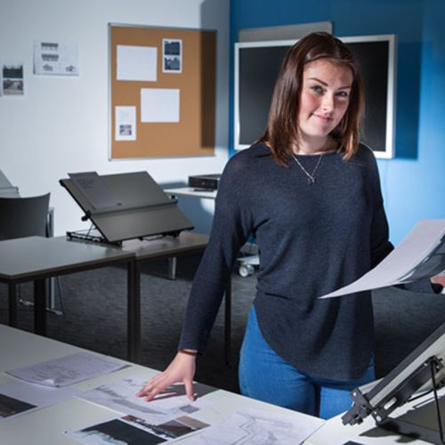 Female Civil Engineering Foundation Apprentice examines work in an engineering office