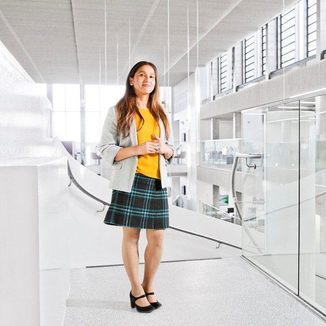 A young woman in a bright white office corridor