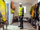 A young male standing and smiling in a hard hat and hi-vis vest during his civil engineering foundation apprenticeship