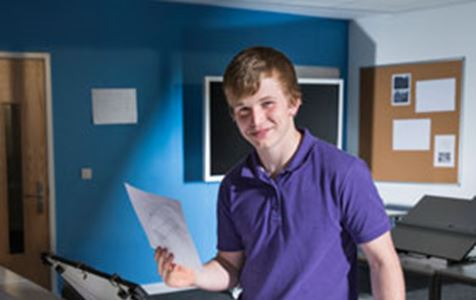 Male Foundation Apprentice William wears a purple polo shirt and holds planning documents in a drawing room for his Civil Engineering course