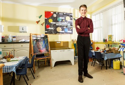 Foundation apprentice Joe stands and smiles in a nursery he works in