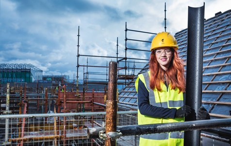 Plumbing apprentice Hanna stands on rooftop scaffolding wearing a hard hat and a high vis vest